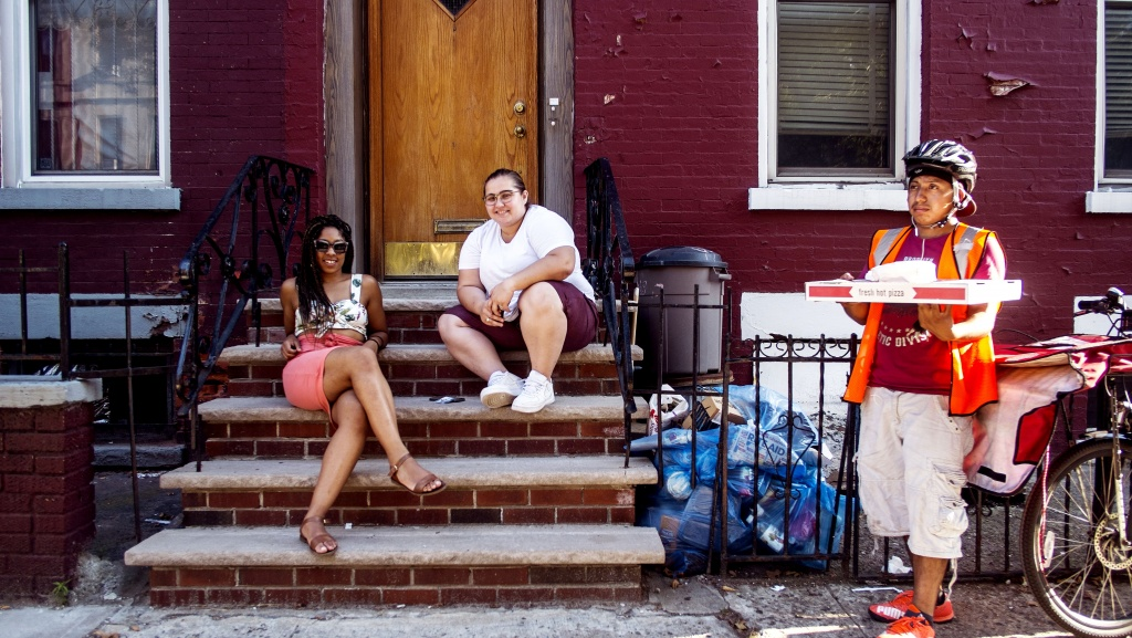 Friends and recent residents Martine (L) and Nicole (R), on the other hand, are so comfortable on Nicole's stoop at Sterling and Franklin that they ordered pizza to it on a sweltering Saturday afternoon.